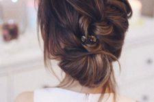 05 a messy diagonal braid updo with bangs and a rhinestone hair pin