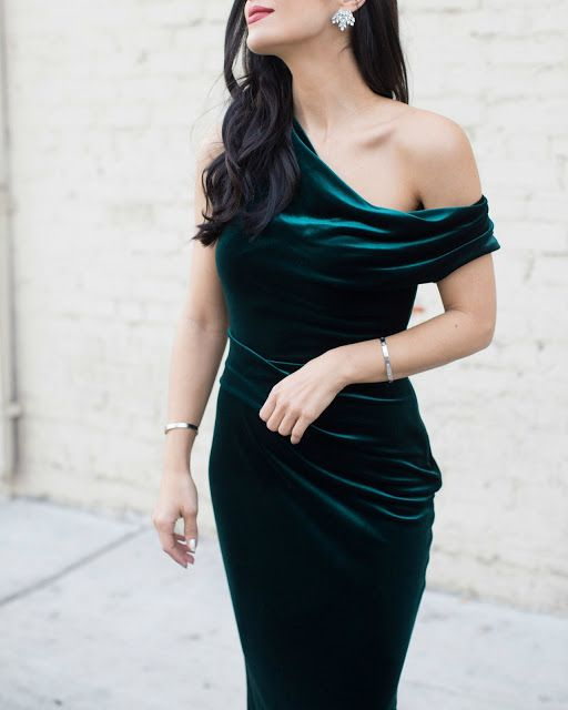 an emerald one shoulder velvet dress and statement earrings is all you need for a party