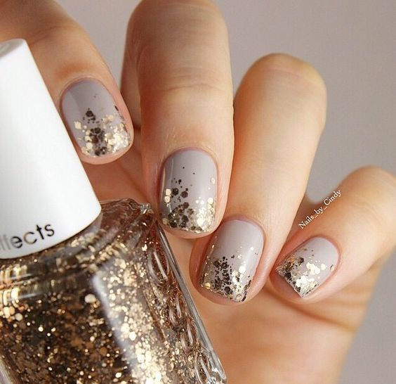 dove grey manicure with gold glitter hexagons for a chic festive look
