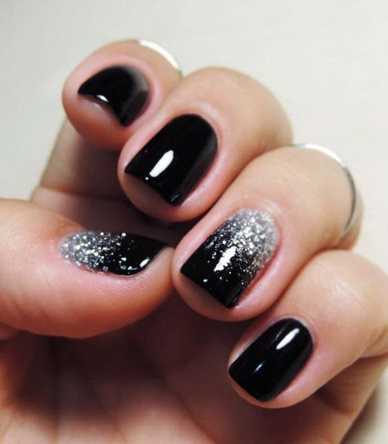 shiny black nails with touches of silver glitter look chic and glam