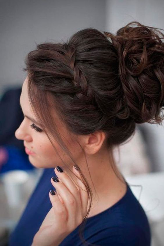 a braided updo with bangs and a curly top knot on the back