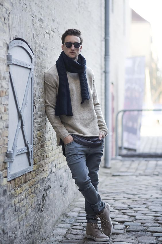a neutral sweater, a navy scarf, grey jeans, brown sneakers for a relaxed feel