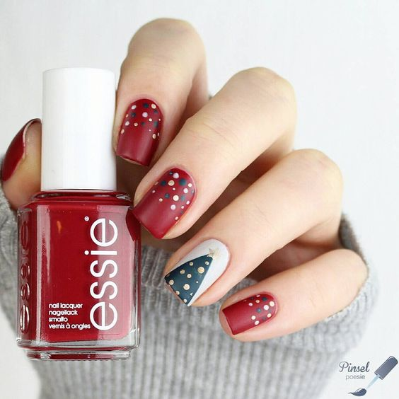 matte red nails with polka dots and an accent white nail with a Christmas tree