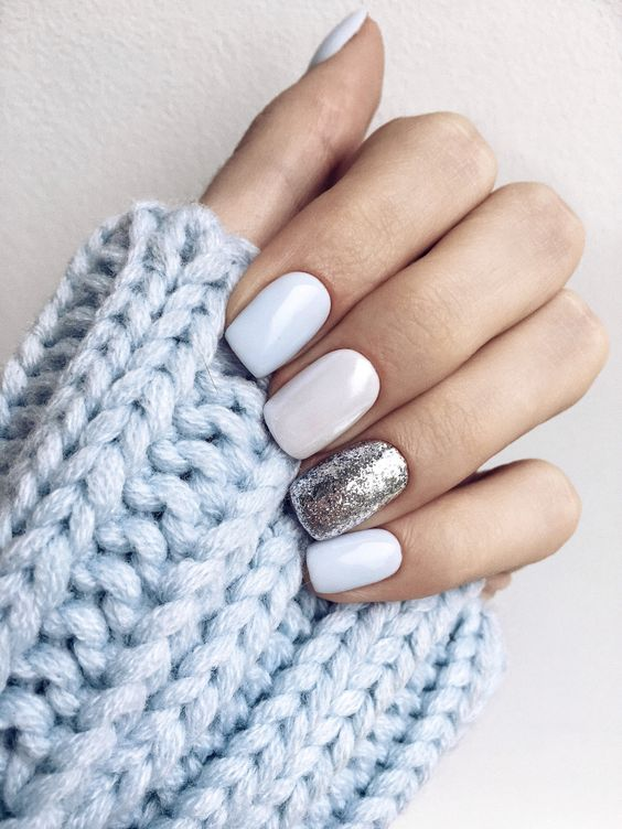 white nails with a silver leaf accent nail look very elegant and winter like