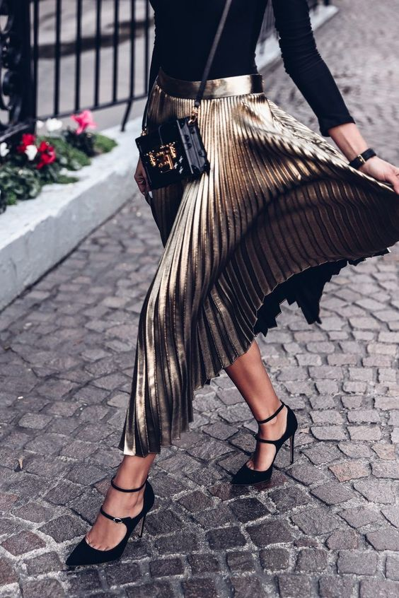 a black turtleneck, a metallic midi skirt and black suede strappy heels