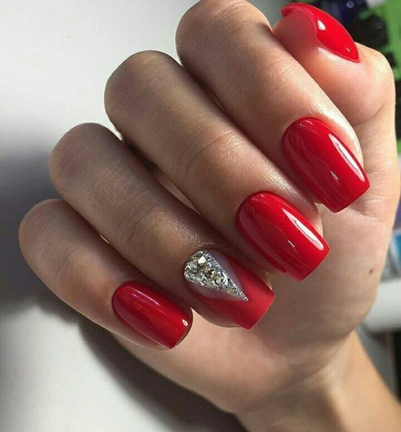 a red manicure, an accent matte nail with large rhinestones for a bold look