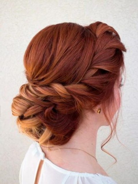 a side braided hair updo with a low braided bun and bangs
