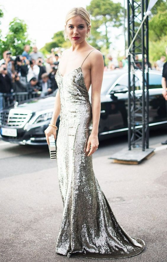 a silver sequin floor-length slip dress paired with drop earrings, a box clutch, and a red lip
