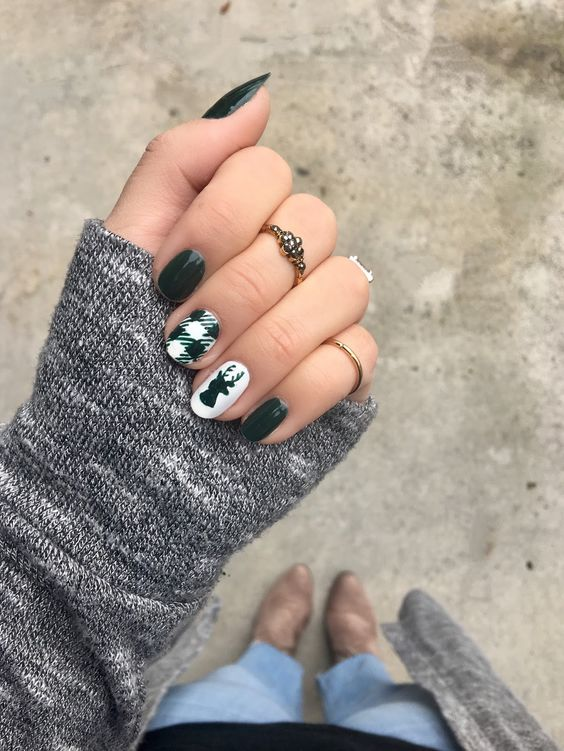green nails with two accents   a deer head and a plaid nail