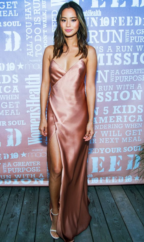 a dusty pink silk slip dress with a thigh-high slit and white sandals create a very sexy look