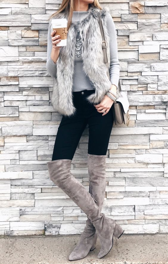 a grey top, a statement necklace, a faux fur vest, black skniies and dove grey boots