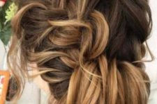 09 a side braid updo with a low chignon and messy wavy hair down