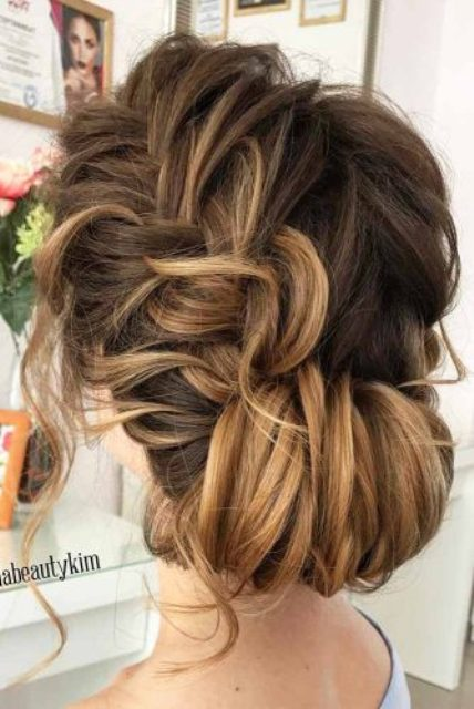 a side braid updo with a low chignon and messy wavy hair down