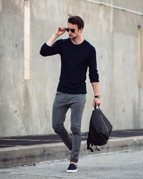 grey jeans, a navy sweater, navy slipons and a black backpack