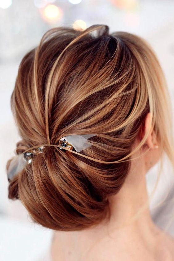 a messy chignon hairstyle with a ribbon and bead hairpiece