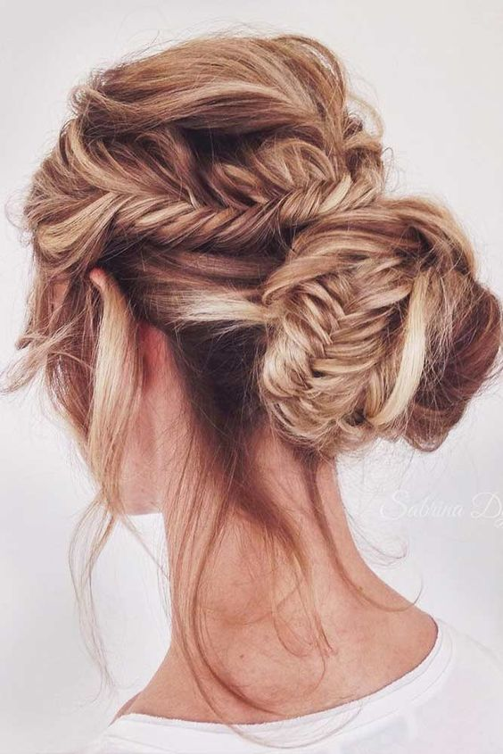 a messy fishtail braid with a low bun and bangs down