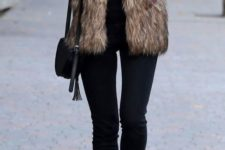 10 a total black look with jeans, a cutout sweater, boots and a bag and a brown faux fur vest