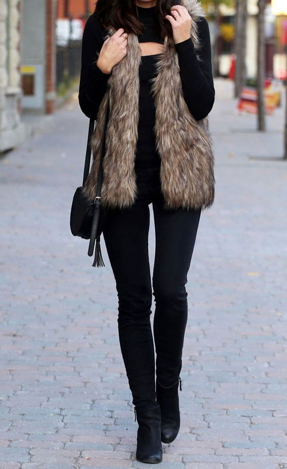 a total black look with jeans, a cutout sweater, boots and a bag and a brown faux fur vest