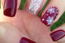 10 red nails with a silver glitter one and a snowflake one look cute and very wintery