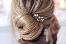 11 a messy low chignon hairstyle with bangs and a rhinestone headpiece