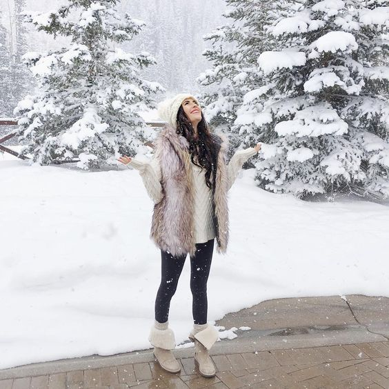 black skinies, a white sweater, a neutral vest, creamy fur boots and a beanie