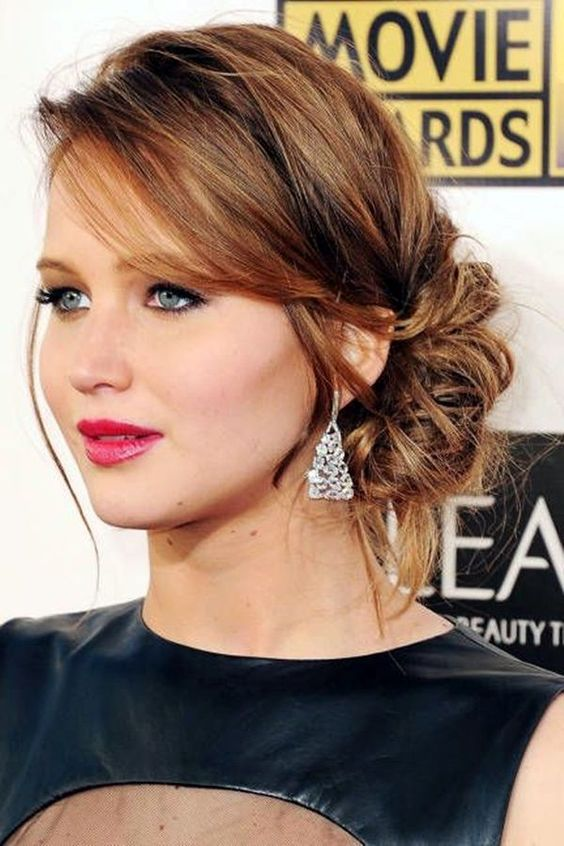 a messy sided low updo with bangs for medium length hair
