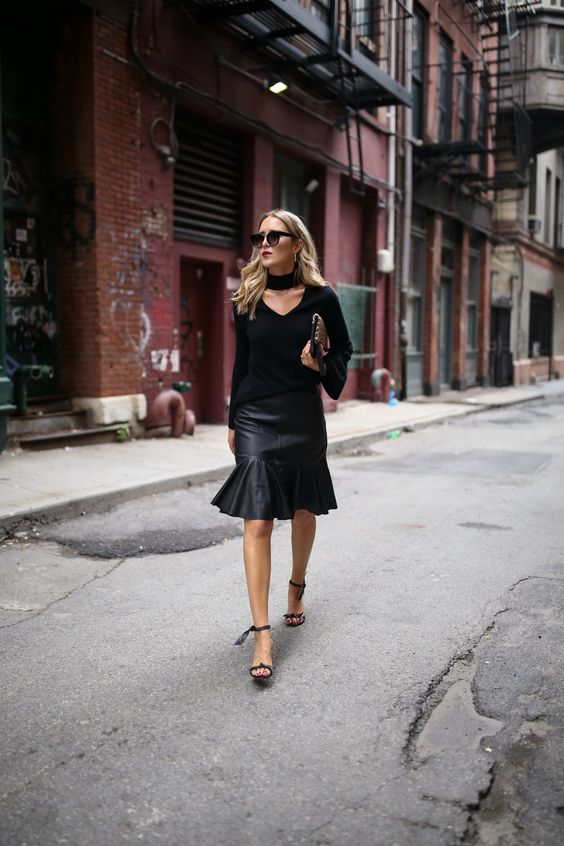 a work outfit with a black cutout cashmere sweater, a black leather skirt and heels