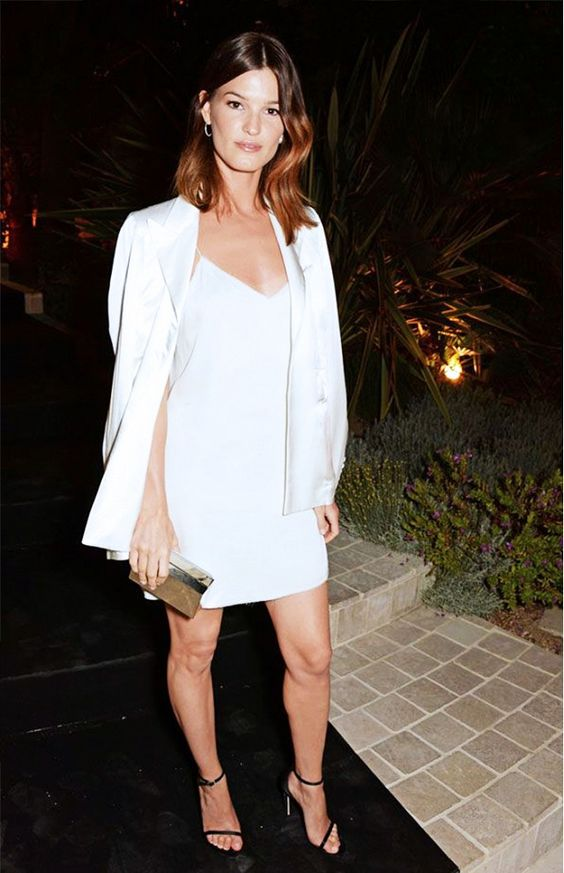 a white slip mini dress with a white blazer over it, black ankle strap shoes and a metallic clutch