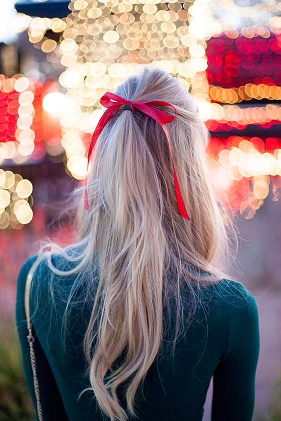 a half updo with a ponytail accessorized with a red bow looks very Christmassy