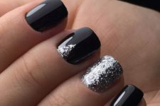 15 shiny black nails with an accent silver glitter one and a small glitter triangle