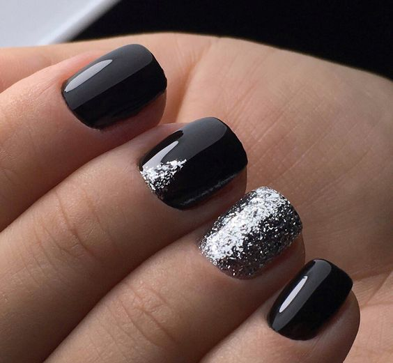 shiny black nails with an accent silver glitter one and a small glitter triangle