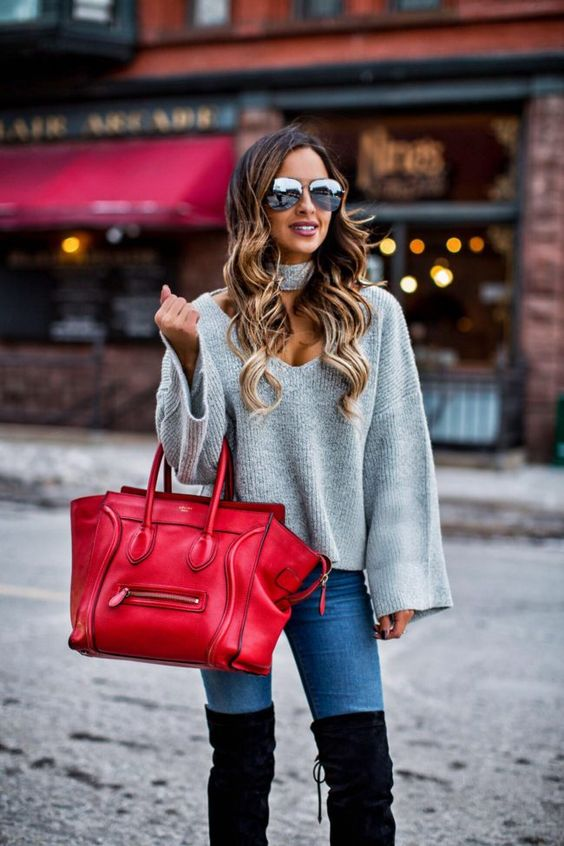 blue jeans, tall black boots and a grey sweater with a cutout neckline