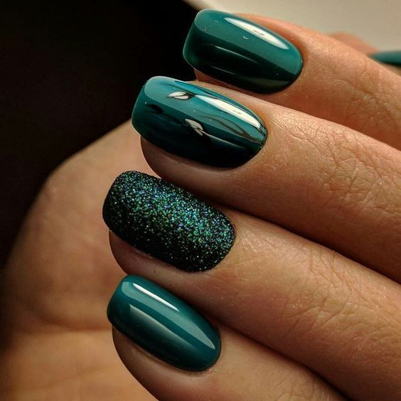 shiny forest green nails with a glitter accent one for holidays