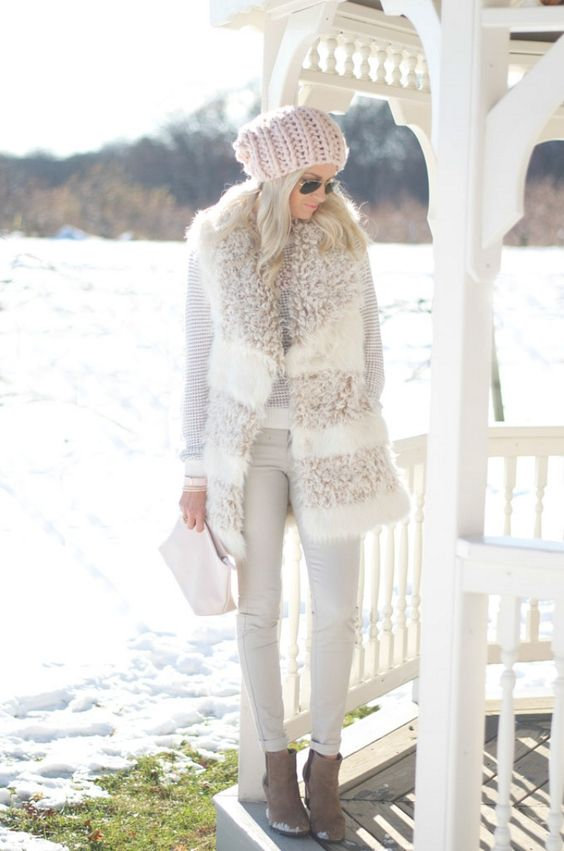 white skinnies, a neutral sweater, a faux fur vest, brown booties and a beanie