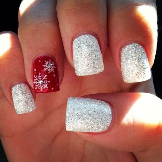 silver glitter nails with an accent red one with snowflakes