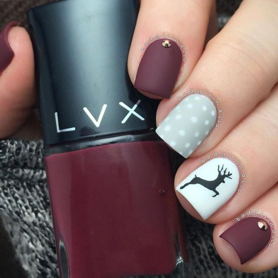 matte burgundy manicure with a grey polka dot and a white deer nail