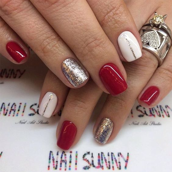 red manicure with silver glitter and white accents