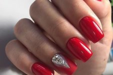 21 a classic red manicure spruced up for the holidays with a rhinestone accent