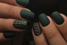25 matte dark green nails with an accent nail lined up with emerald rhinestones