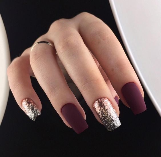 Picture Of matte burgundy nails and gold glitter ones look very eye catching and unusual