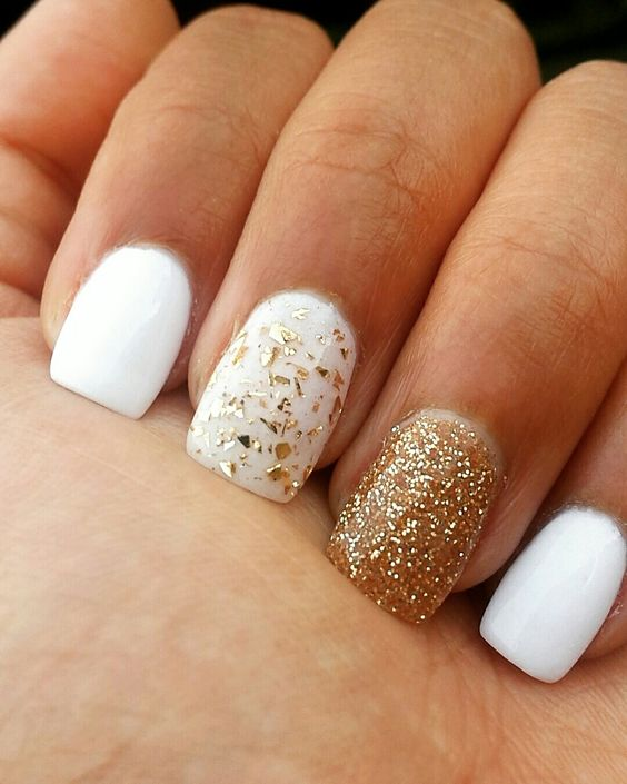 white nails with a glitter gold one and a gold leaf one for a chic shiny look