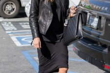 With black leather jacket, black shirt, knee-length skirt, boots and leather bag