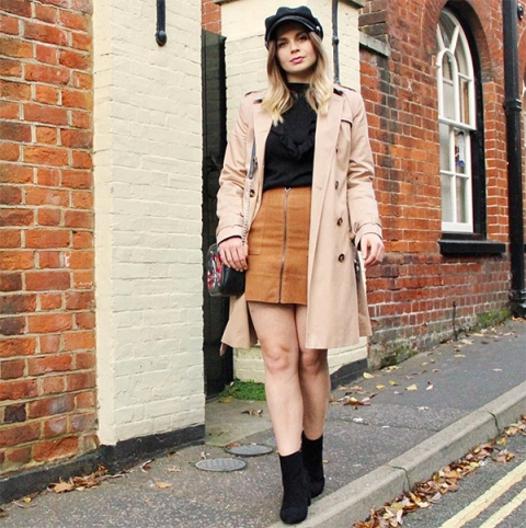 With black shirt, brown skirt, beige coat and black ankle boots