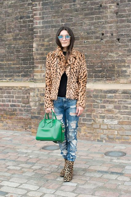 With black shirt, distressed jeans, leopard printed boots and green bag