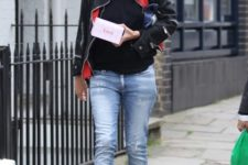 With black shirt, leather jacket, cuffed jeans and fringe boots