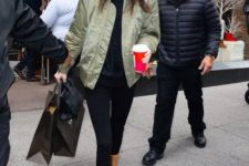 With black shirt, olive green jacket, black leggings and shearling hat