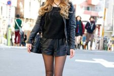 With black shirt, platform shoes, cap and leather jacket
