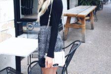 With black shirt, printed mini skirt, white bag and black boots