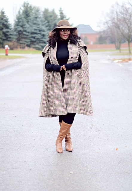 With black turtleneck, black pants, brown leather boots and beige hat