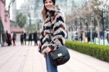 With faux fur coat, beanie, skinny jeans and black leather bag